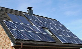 A roof that uses solar energy three ways - solar power panels, solar hot water heating, and a skylight.
